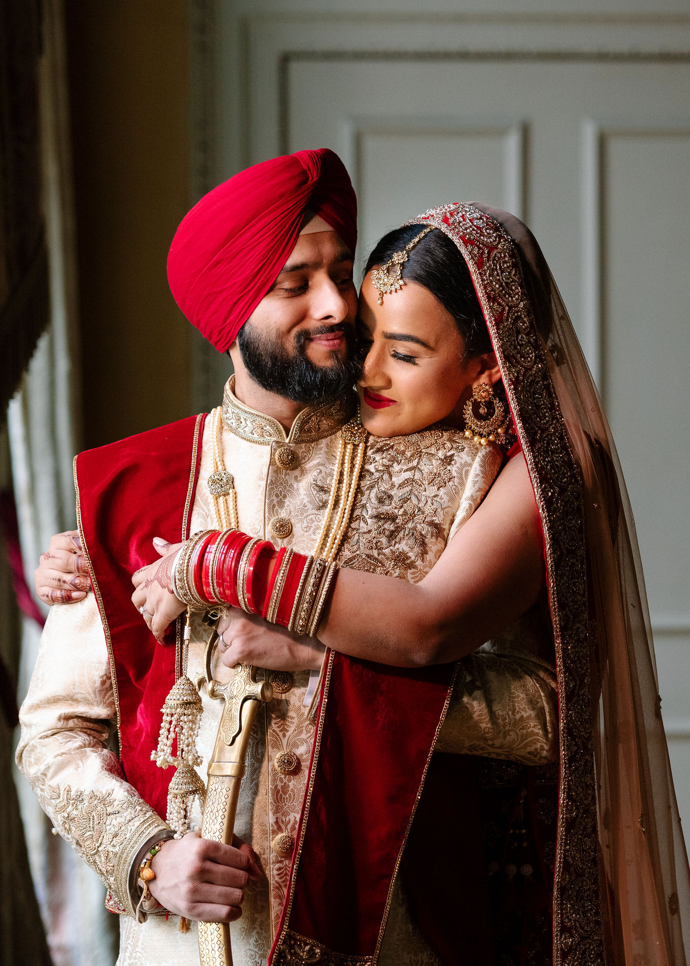 Bride is hugging with a hand the groom from the back laying her chin on his shoulder. Groom has his kirpan in his hand