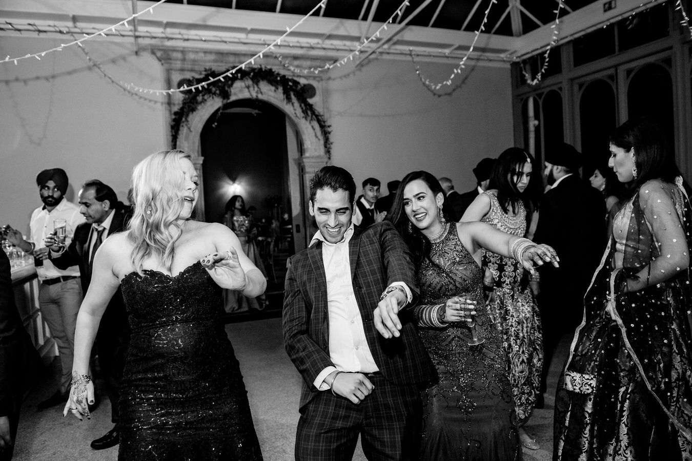 Bride with a glass of champagne in hand is dancing along with her wedding guests.