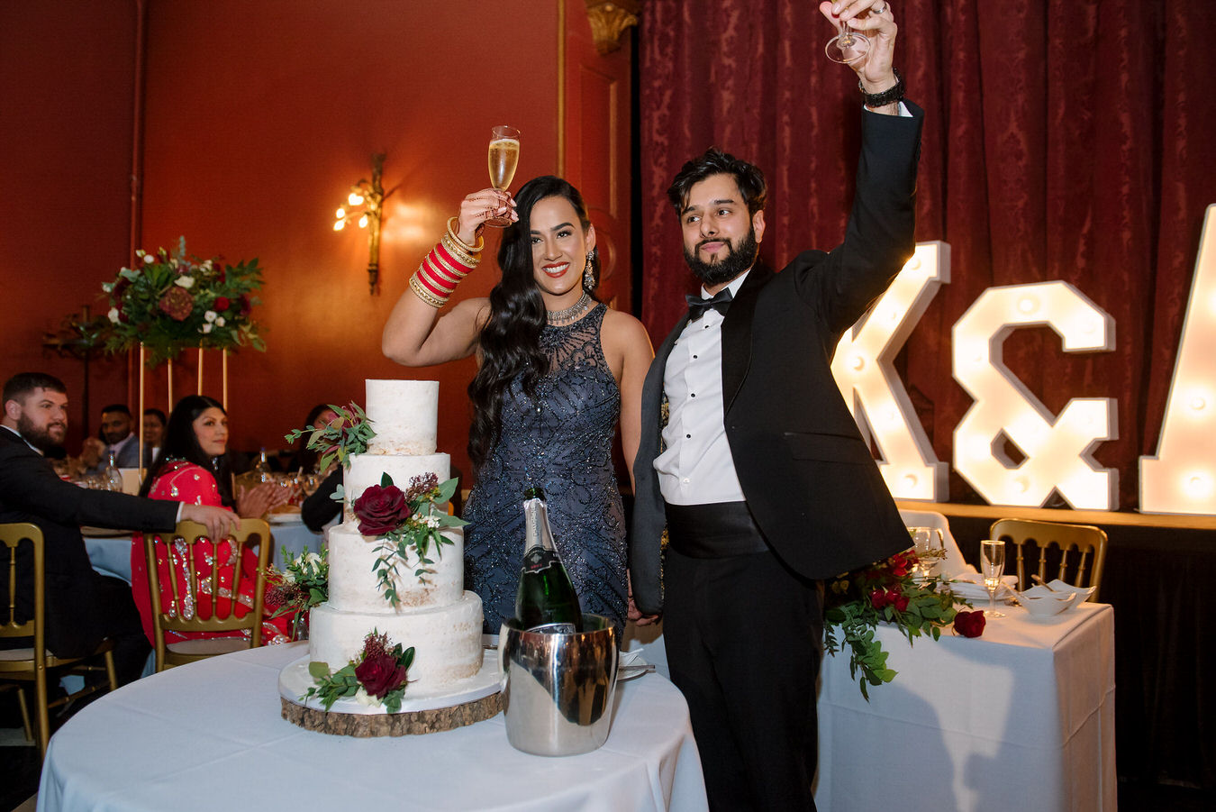 Bride and groom are lifting the glasses up cheering after cutting their wedding cake.