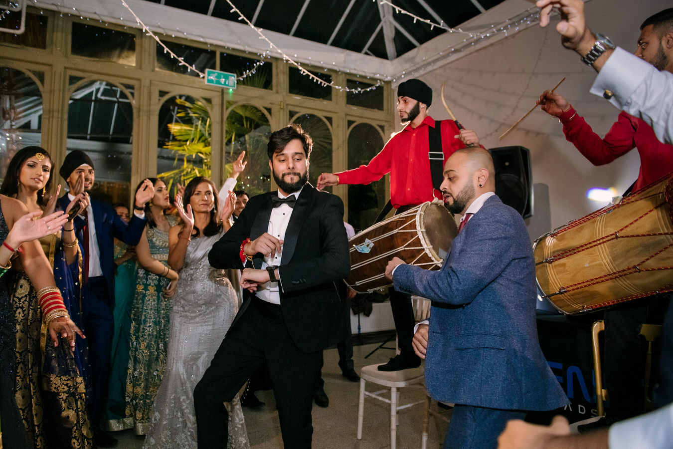 Groom and the wedding guests are moving in the rhythm of the Indian music at Hampton Court House