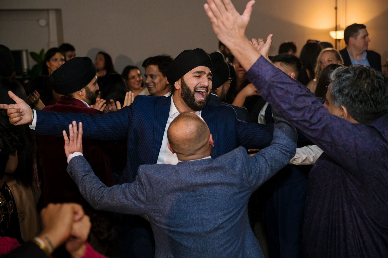 Sikh Asian wedding man's are singing Indian songs with their arms up in the air.