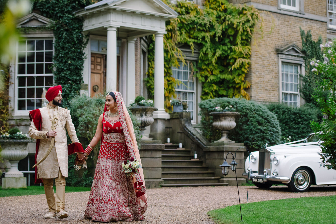 Bride dressed in a bridal lehenga and groom in a Punjabi outfit with kirpan walking hand in hand during their Sikh wedding at Hampton Court House