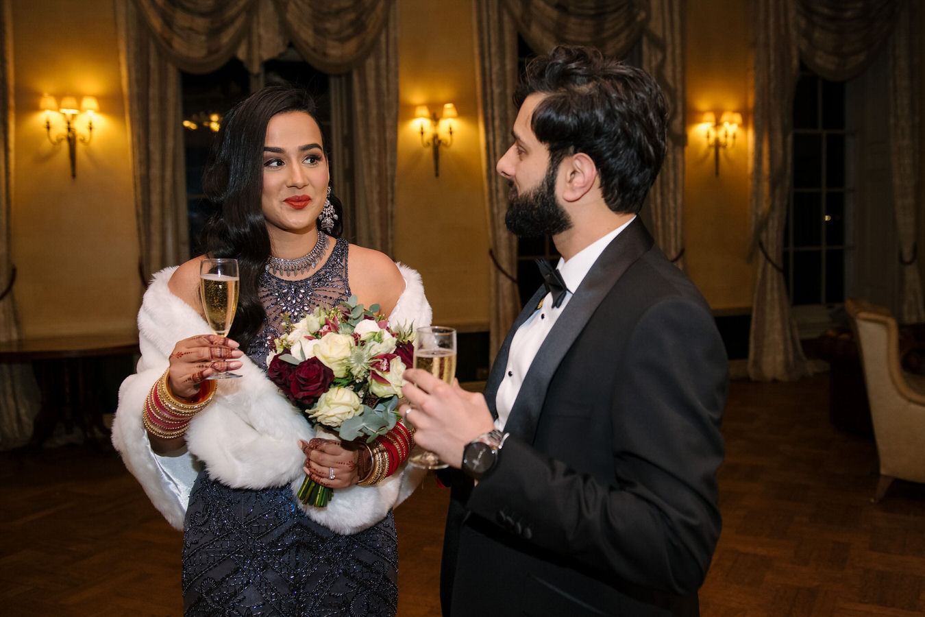 Asian bride dressed in a grey sparkling evening dress and the groom with champagne glasses in their hands are looking at each other