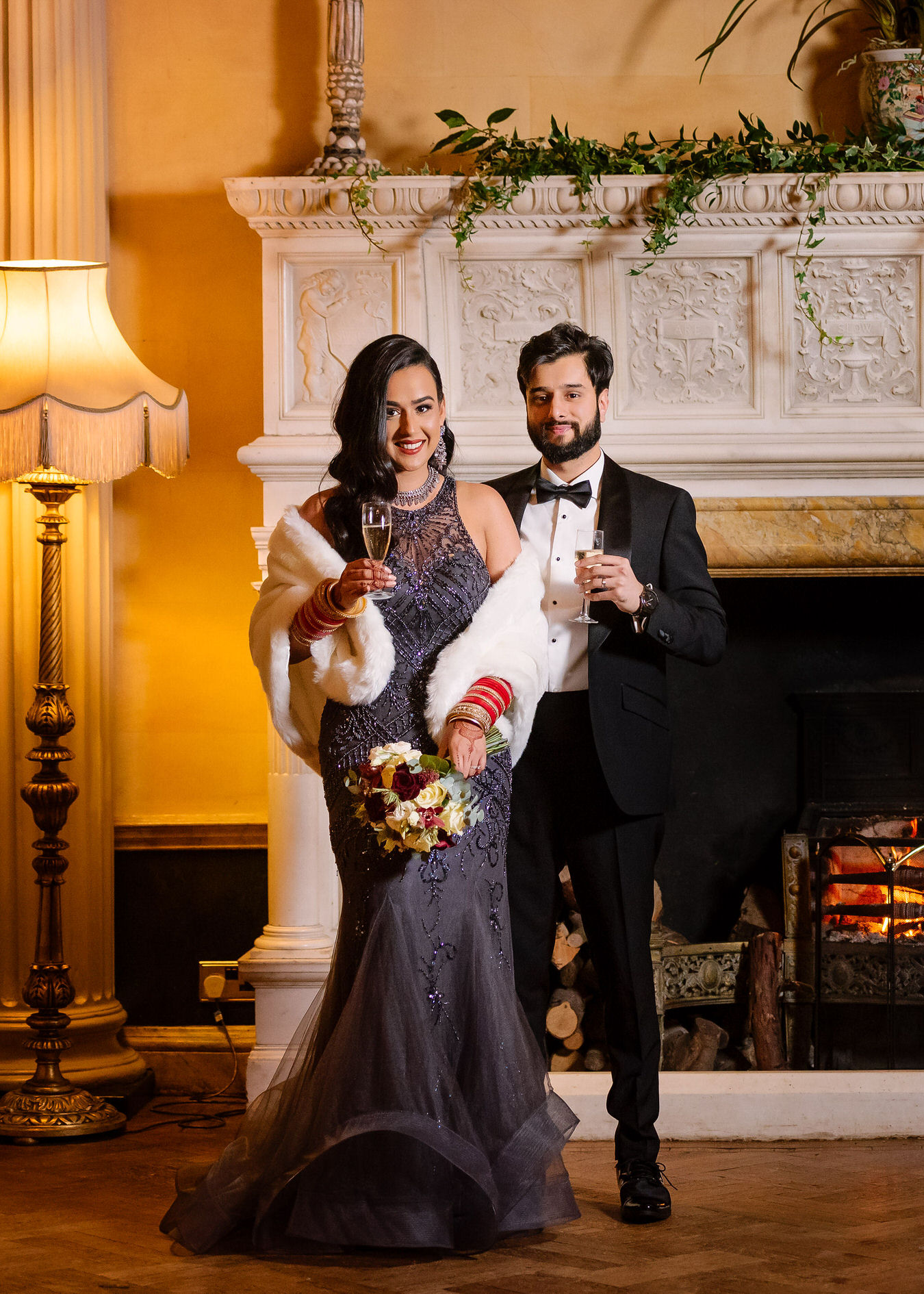 Asian wedding bride and groom with champagne glasses standing in front of the fireplace