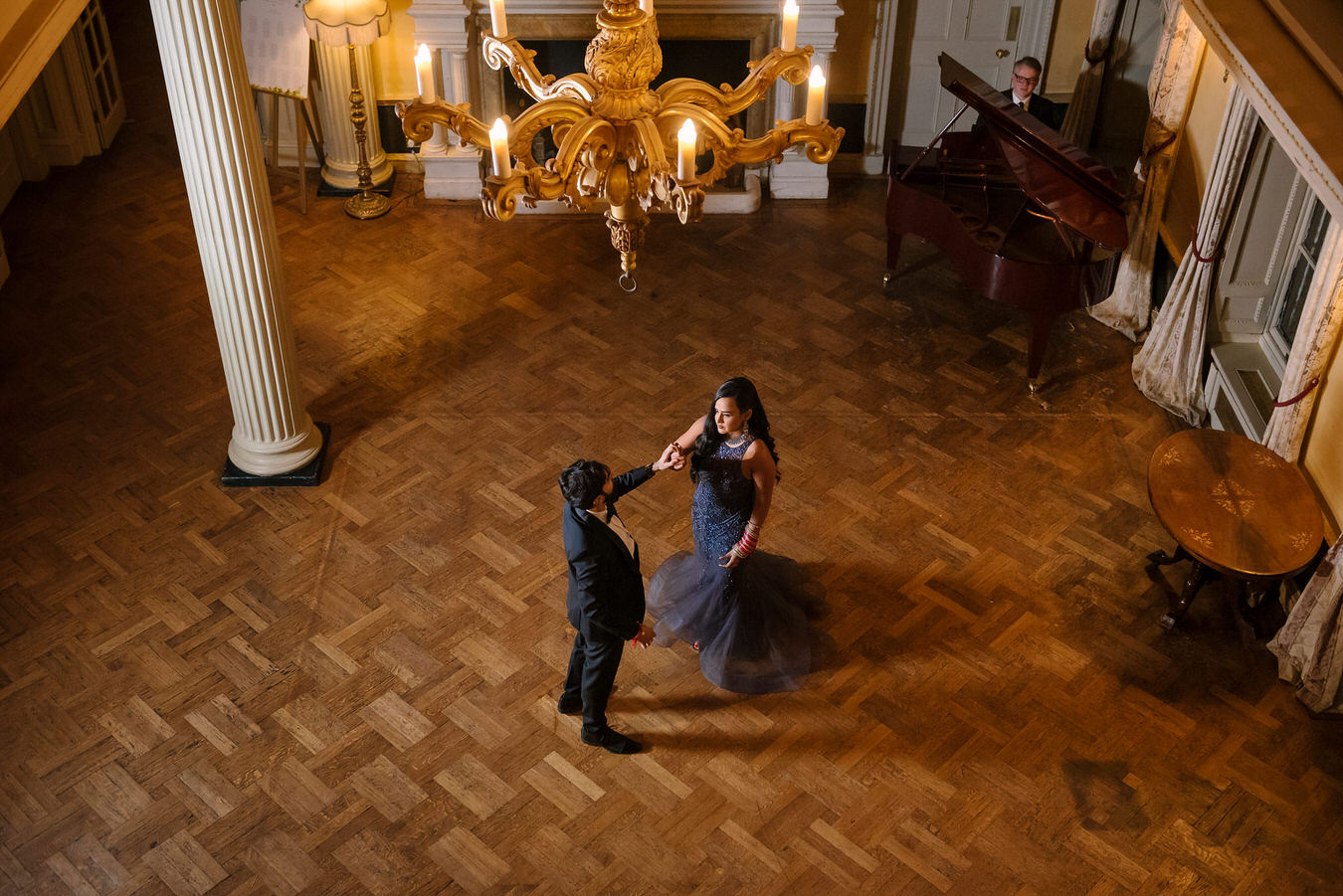 Hampton Court House Wedding photography of bride & groom from upstairs as they are dancing in the middle of the room