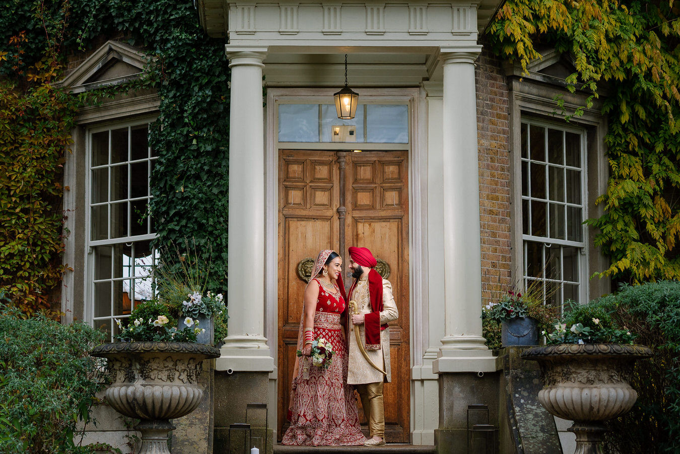 Asian Sikh wedding bride, with a bouquet in her hand and groom holding his kirpan with his left hand on the stairs at Hampton Court House.