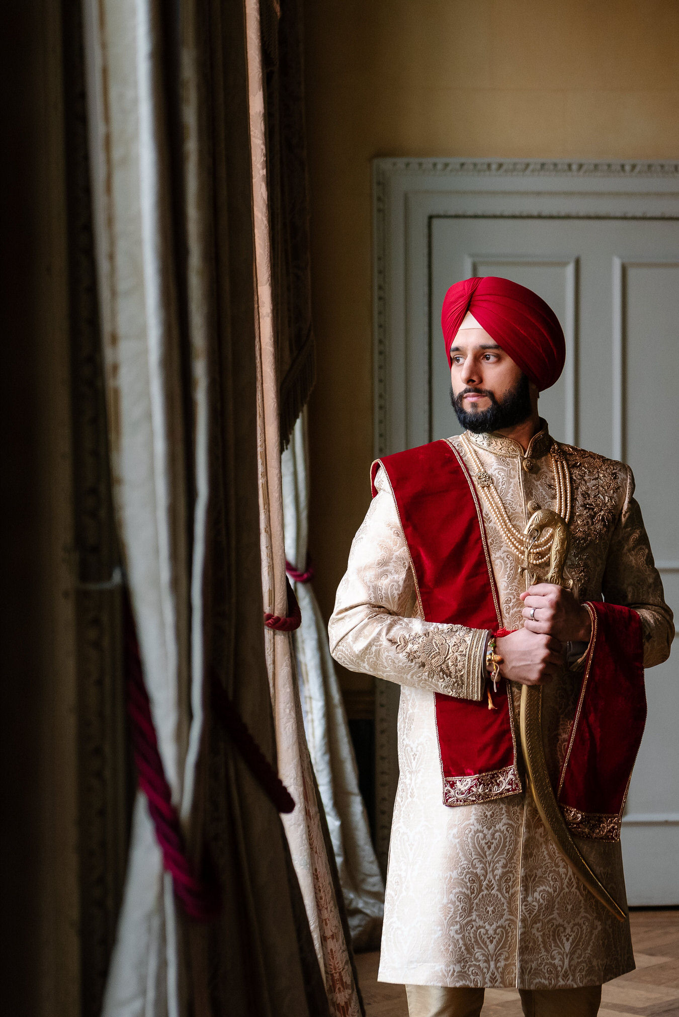 Sikh wedding groom with kirpan in his hands and a red turban on the head looking at his right.