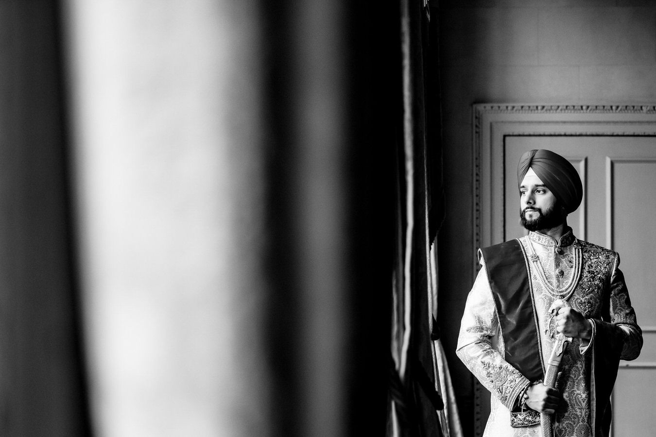 Sikh wedding black and white photography of a groom with kirpan in his hands and a turban looking at his right.