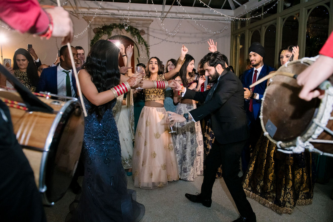 Asian wedding couple dancing with glasses in their hands along with other guests. Asian Dhol drummers are playing in the foreground.