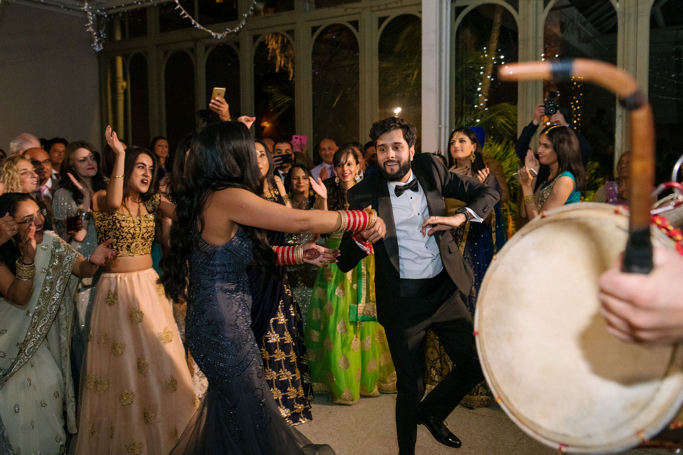 Sikh Asian wedding couple are dancing in the middle of the dancefloor and other guests applaud around. In the foreground there is a Dhol Drum.