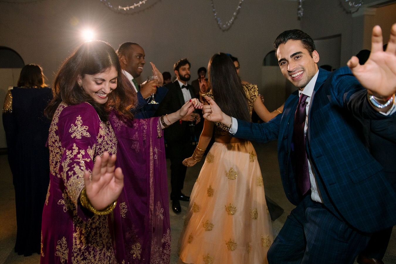 Wedding guests are dancing and feeling good at the Sikh Asian wedding.