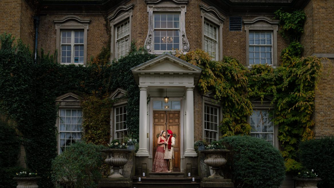 Wedding photography Asian bride & groom in front of Hampton Court House