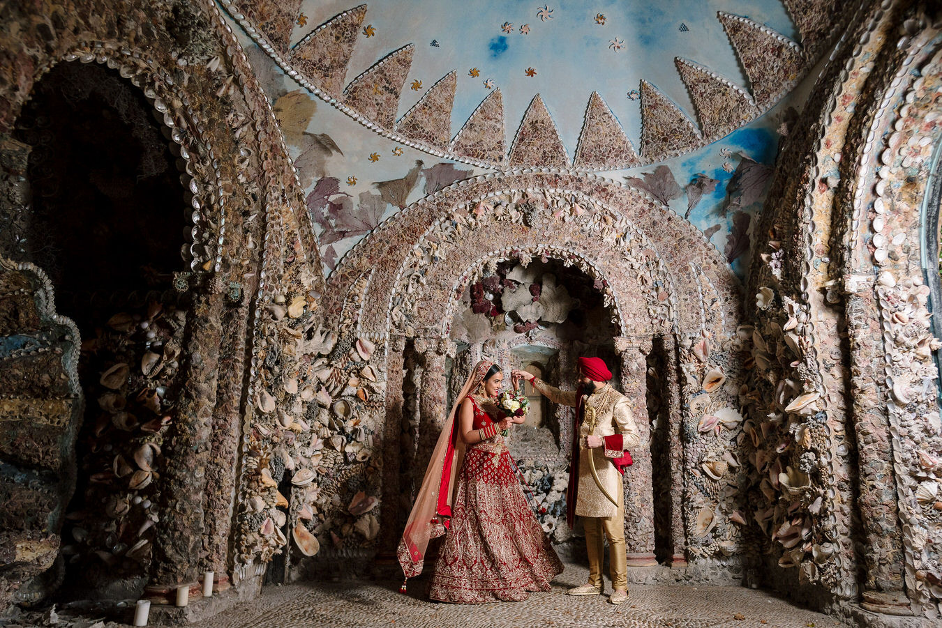 Sikh Asian wedding groom with his kirpan in hand and a bride with a bouquet are dancing inside the shell grotto