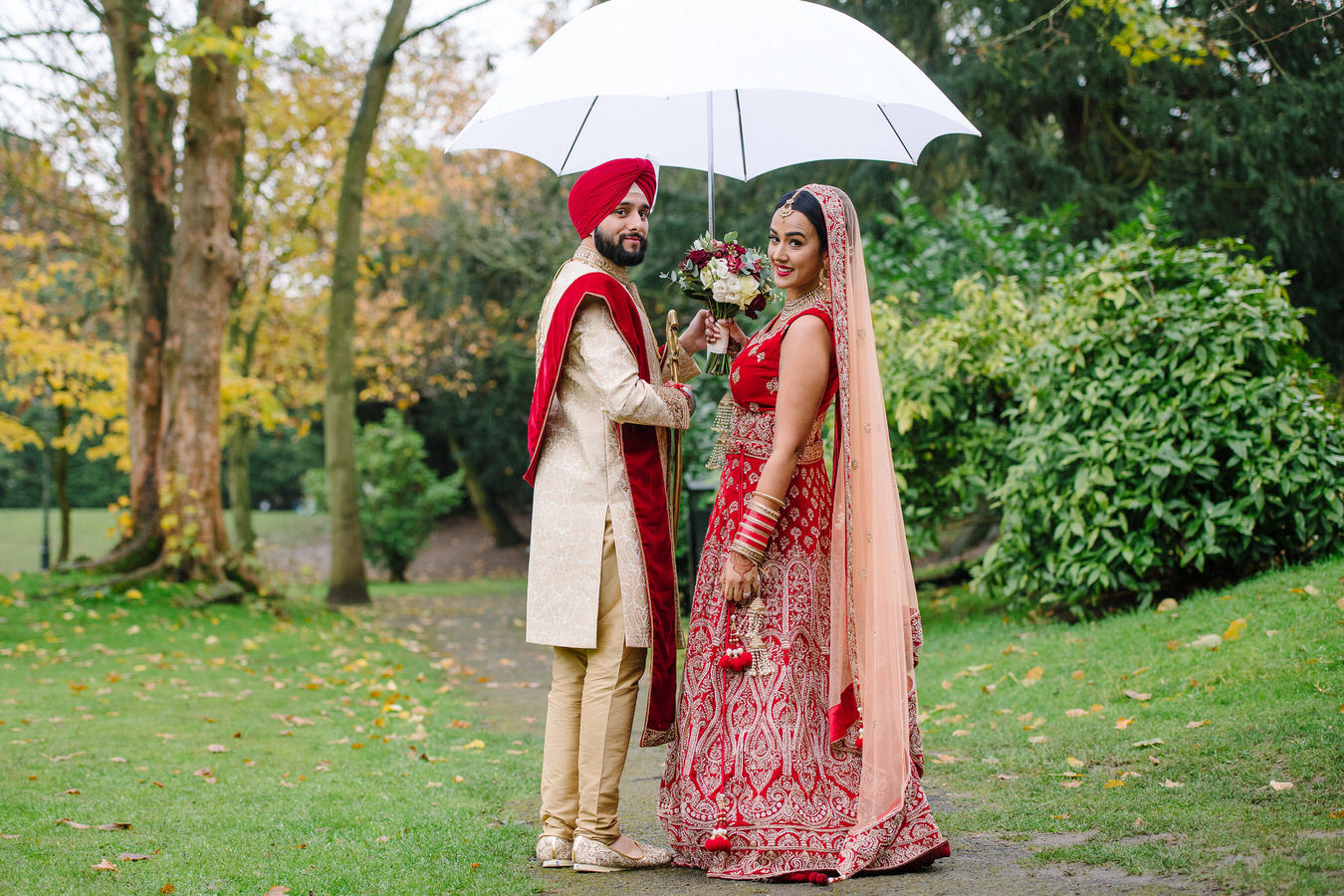Sikh Asian wedding bride and groom in the garden holding a white umbrella and a bouquet in hands